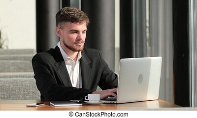 Businessman working at his laptop in a small cafe