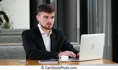 Office worker to make calls at a table in a cafe - Young man...