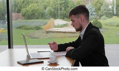 Young man working with securities at a table in a cafe -...