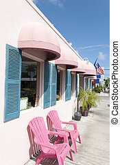 Key West Pink Street - Pink color building and two chairs on...