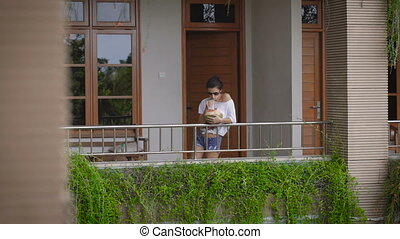 Girl in sunglasses came out onto the balcony of his room to...