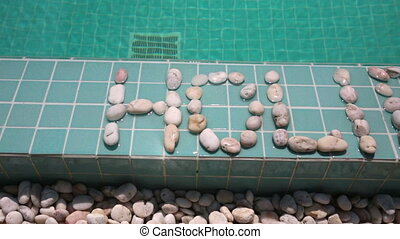 The inscription holiday is laid out by pebble on a pool...