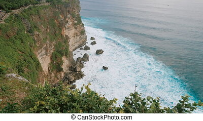 Scenic view of high cliff and deep blue sea at the foot of the rock. Breathtaking panoramic scene of high mountain view and endless water surface of the ocean.