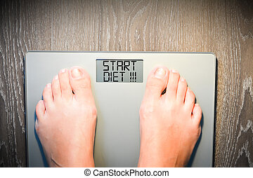 Help to lose kilograms with woman feet stepping on a weight...