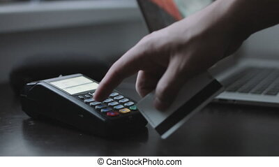Man uses credit card terminal in office. - Man uses credit...