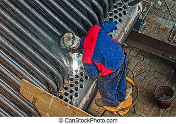 Welder welding metal pipes. Over shoulder shot.