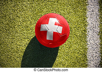 football ball with the national flag of switzerland lies on...