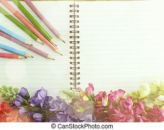 notebook pencil and flowers background made with filters...