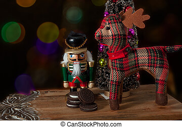 Nutcracker dressed in uniform beside the deer of Santa -...