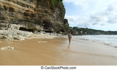 Cute girl in a striped shirt is walking on a sandy beach along the rocky walls. Young woman turns around and looks at the waves that rolled ashore.