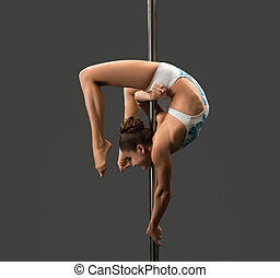 Young girl hangs upside down on pylon in studio