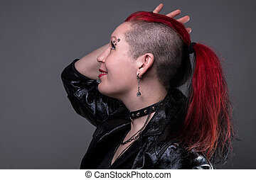 Punk woman with shaved head on gray background