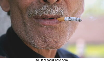 Tanned adult man smoking cigarette outdoors. Close-up....