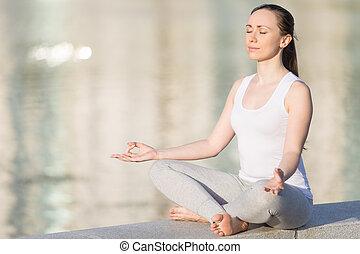 Sukhasana pose against water background - Sporty beautiful...
