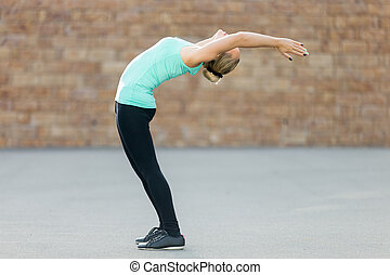 Standing Backward Bend pose - Sporty beautiful young woman...