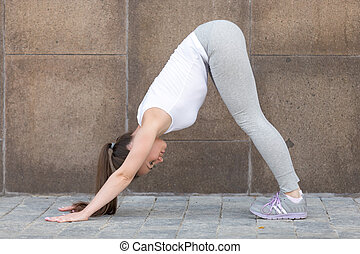 Downward facing dog exercise against the wall - Sporty...