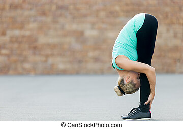 Standing forward bend pose - Sporty beautiful young woman...