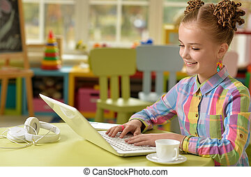 little girl using laptop typing and smiling