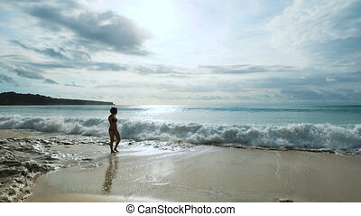 Slender girl walking on the sandy beach along the coast of the ocean which rolled the big waves. Young woman nearly knocked the legs with water.