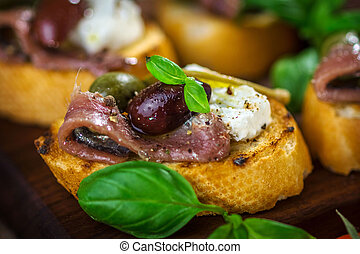 Tasty bruschetta with anchovy, caper, olive oil ...