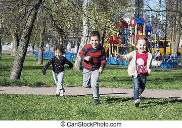 Spring begaayut children on the grass near the playground.