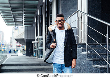Young african man wearing backpack walking on the street -...