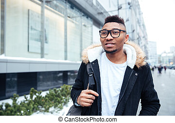 Handsome african young man walking on the street. - Photo of...
