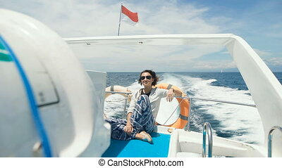 Cute girl sitting in the back of a motor boat enjoys walking...