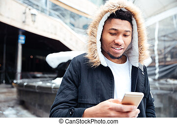 Handsome african man walking on the street while using phone...