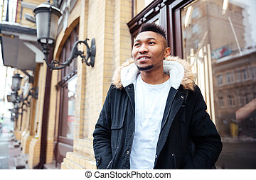 Handsome african young man walking on the street - Picture...