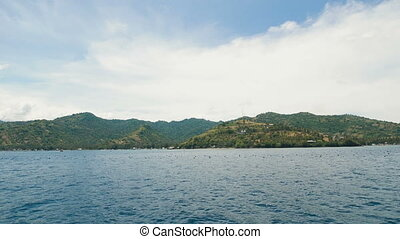 A view of the blue sea with small waves and an island with lots of trees and green grass the sky is blue and clouds is white