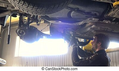 auto mechanic repair automobile against intensive light. -...