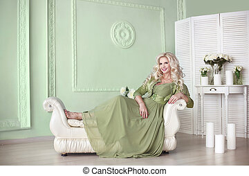 Beautiful smiling elegant blond woman with long curly hair style wears in green dress