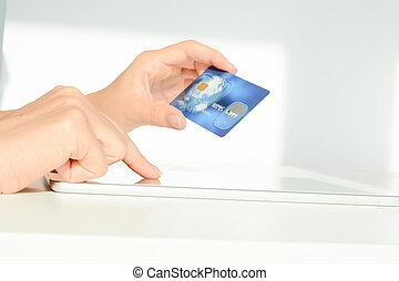Close-up of Woman hand holding a blue credit card using an...