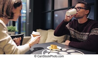 couple eating cake and drinking coffee at cafe - food,...