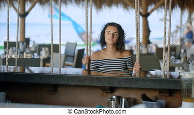 Pretty brunette sitting at the creative bar in the hotel complex. Restaurant using swing instead the chairs. Young woman with beautiful eyes gazes off into the distance.