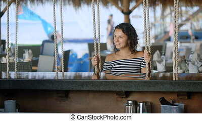 Brunette in a striped blouse with bare shoulders sitting at...