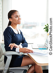 Vertical image of african business woman on armchair