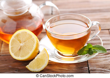 Cup of tea with mint and lemon on brown wooden table