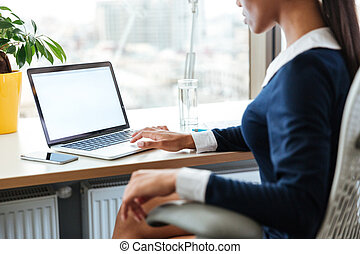 Cropped image of business woman using laptop - Cropped image...