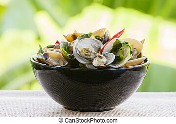Cooked mussels with green leaves and red pepper in a black...