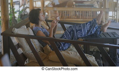 Activities on the island of Bali. A girl with short hair in a striped T-shirt and baggy trousers sitting in an easy chair, put his feet on the table. It relaxes and relieves beautiful views on your phone.