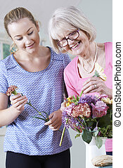 Senior Woman With Teacher In Flower Arranging Class