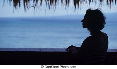 Silhouette of a girl who looks into the distance against the blue ocean. Young woman admires the resort's tropical scenery and straightens her hair.