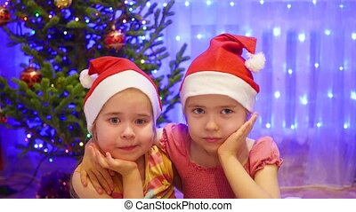 Two cute girls smiling and waving at the camera in a Santa hat. In the background, lights and garlands of Christmas fir
