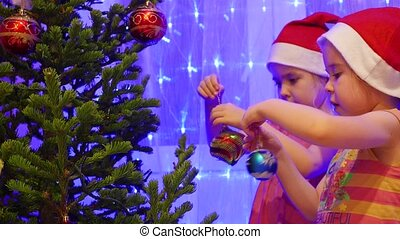Two sisters beautiful girls decorate a Christmas tree with...