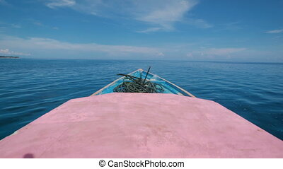 View of the front of the boat is moving rapidly into the distance in ocean. Blue salt water and beautiful sky with white cloud.