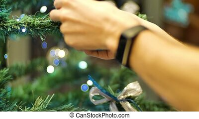 Female hands hanging balls on the Christmas tree. Winter...