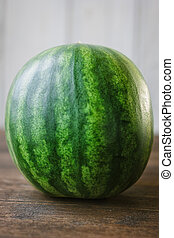 Whole undivided watermelon on white background. Small green...