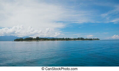 View from a boat on a small island with lots of trees and...